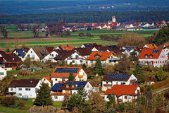 Solar energy panels on roofs of country village. Country village with homes benefiting from their solar power. Modern green living in German countryside royalty free stock photo