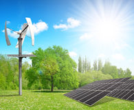 Solar energy panels with wind turbine in spring landscape. Royalty Free Stock Images