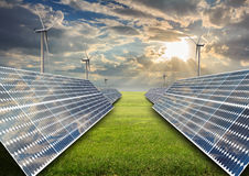 Solar energy panels and wind turbine in sunset. Stock Photo