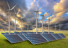 Solar energy panels and wind turbine in sunset. Royalty Free Stock Photos