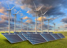 Solar energy panels and wind turbine in sunset. Royalty Free Stock Photo