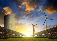 Solar energy panels, wind turbines and nuclear power plant. At sunset Stock Photo