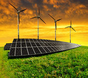 Solar energy panels with wind turbines. In the setting sun royalty free stock photo