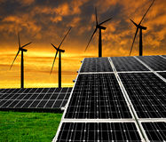 Solar energy panels with wind turbines. In the setting sun royalty free stock images