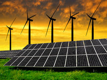 Solar energy panels with wind turbines. In the setting sun royalty free stock photography