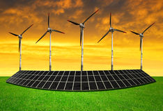 Solar energy panels with wind turbines. In the setting sun royalty free stock image