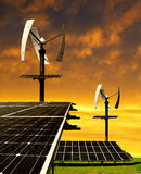 Solar energy panels with wind turbines. In the setting sun stock photo