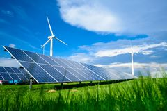 Solar energy panels and windmills against blue sky on summer day. Background royalty free stock photos