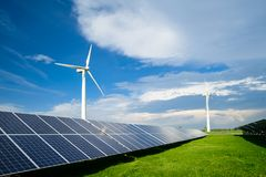 Solar energy panels and windmills against blue sky on summer day. Background stock image