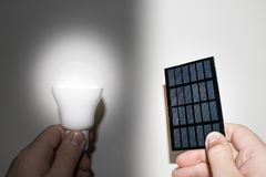 Solar panel and light bulb in hand. Solar energy photovoltaic panel and light bulb in hand Royalty Free Stock Photo