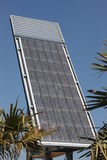 Solar Energy Station. Large Modern Solar Panel surrounded by sub tropical plants and deep blue sky stock images