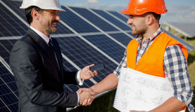 At solar energy station business client and foreman shaking hands. Two men making deal, shaking hands, solar panels on backstage royalty free stock photography
