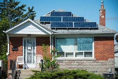 Solar Energy Use in Private House. Solar energy panels in private house, practical  use of solar energy is becoming more popular in Canada, some houses and Stock Photo