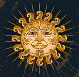 Solar face on a black background. Gold sun with a smiling face on a dark background Stock Photo