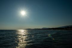 Solar flare, beach, ocean. View from the yacht to the coast of Montenegro stock images