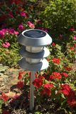 Solar Garden Light. In bed of red impatiens Stock Photo