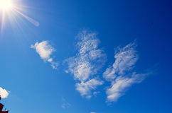 Solar glare and rays in the blue sky. Stock Photos