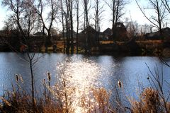 Solar glare reflected in the lake and village in the background. Stock Photography