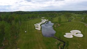 Solar Golf cart with clouds on blue sky and forest lake Golf club, aerial stock footage