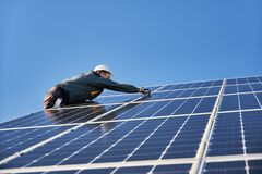Free Solar Installer Working Under Beautiful Blue Sky. Stock Photography - 183368712