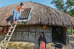 Solar Light. A man cleaning solar plate of Sundarban in India Royalty Free Stock Images