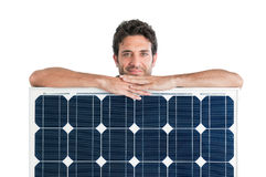 Solar panel. Smiling man showing and holding a solar panel isolated on white background