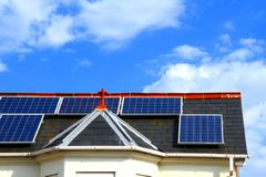 Solar panel. On top of a roof with blue sky in the background Royalty Free Stock Photo