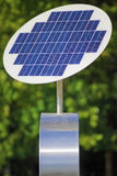 Solar panel. A photovoltaic solar panel with green leaves in the background Stock Photo