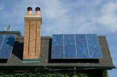 Solar panel. On a roof of old-fashioned house with chimney stock photo