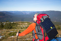 The solar panel attached.The man sitting next to mobile phone charges from the sun. Royalty Free Stock Photo