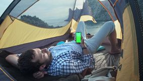 The solar panel attached to the tent. The man sitting next to mobile phone charges from the sun. A young guy lies in a. Camp tent, holding a smartphone with a stock footage
