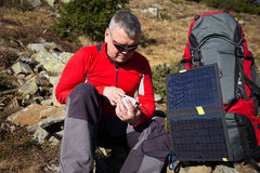 The solar panel attached to the tent. The man sitting next to mobile phone charges from the sun. Royalty Free Stock Images