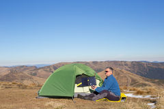 The solar panel attached to the tent. The man sitting next to mobile phone charges from the sun. Royalty Free Stock Photography