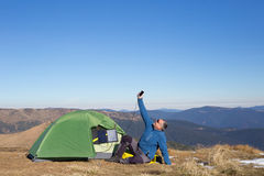 The solar panel attached to the tent. The man sitting next to mobile phone charges from the sun. Stock Photography