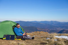 Solar panel. The solar panel attached to the tent. The man sitting next to mobile phone charges from the sun Royalty Free Stock Photos