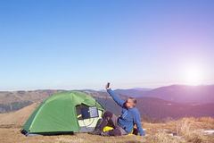 The solar panel attached to the tent. The man sitting next to mobile phone charges from the sun. Stock Photo