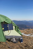 The solar panel attached to the tent. The man sitting next to mobile phone charges from the sun. Stock Image