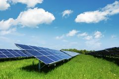 Solar panel on blue sky background. Green grass and cloudy sky. Alternative energy concept Stock Photography
