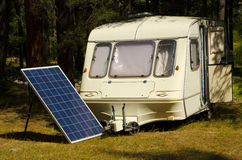 Solar panel in a camping with old caravan on the river bank. Solar panel in a camping in a pine forest with old caravan royalty free stock images
