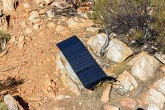 solar panel in campsite on a rock to charge phones and camera, alternative electricity source - concept of sustainable resources stock photography