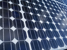 Solar panel cells blue sky copy space. Solar panel photovoltaic cells array close up with cumulus clouds reflected in the panels and copy space. Solar energy is stock photos