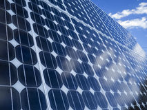 Solar panel cells blue sky copy space. Solar panel photovoltaic cells array with blue sky and cumulus clouds reflected in the panels and copy space. Solar royalty free stock images