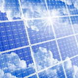 Solar panel, clear sky & sun reflection. Solar panel with reflection of clouds, clear sky and bright sun Stock Photo