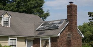 Solar Panel in disrepair on a Home. A home has a solar panel installed that is fallen in a state of disrepair and is not actively generating power Royalty Free Stock Images