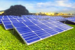 Solar Panel Ecological Renewable Energy. Solar panels spread across the field on the green grass. In the background the city for which energy is provided royalty free stock images