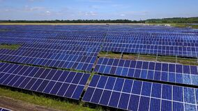 Solar panel farm generating electricity for national grid with a motion graphic indicator of battery charging. New green