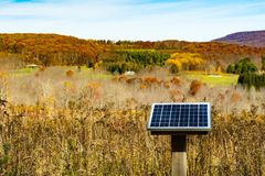 Solar Panel in a farmfield in New York. A solar panel charging an outhouse on a farm in New York Stock Photos