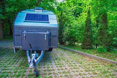 Solar panel is fixed on the tourist trailer. Off-road trailer stands in the parking lot on the background of thick green foliage. royalty free stock image