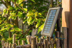 Solar panel in the garden, providing three led-lights with energy Royalty Free Stock Image