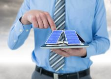 Solar panel on hand of businessman. Digital composite of solar panel on hand of businessman Stock Photo